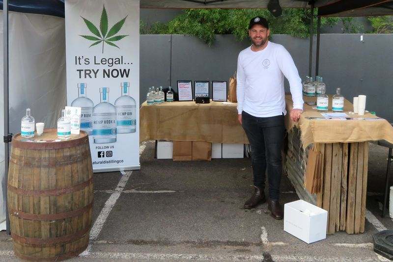 Rhys Staley standing with hemp spirits products