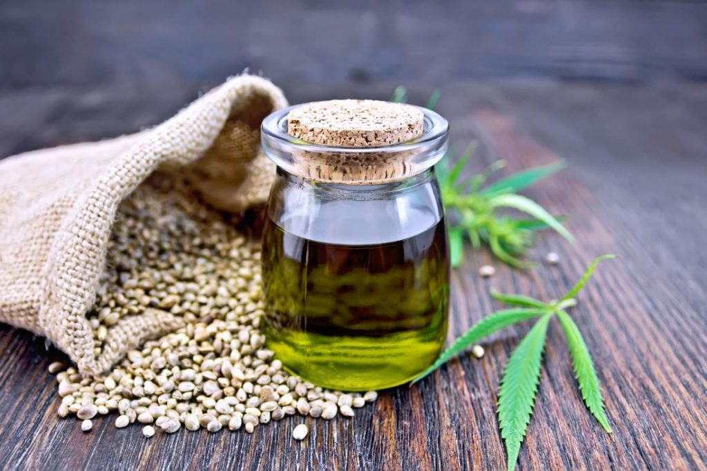 hemp oil in jar with hemp seeds and hemp leaf