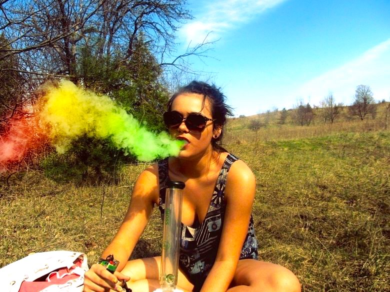 Beautiful girl smoking cannabis from a bong