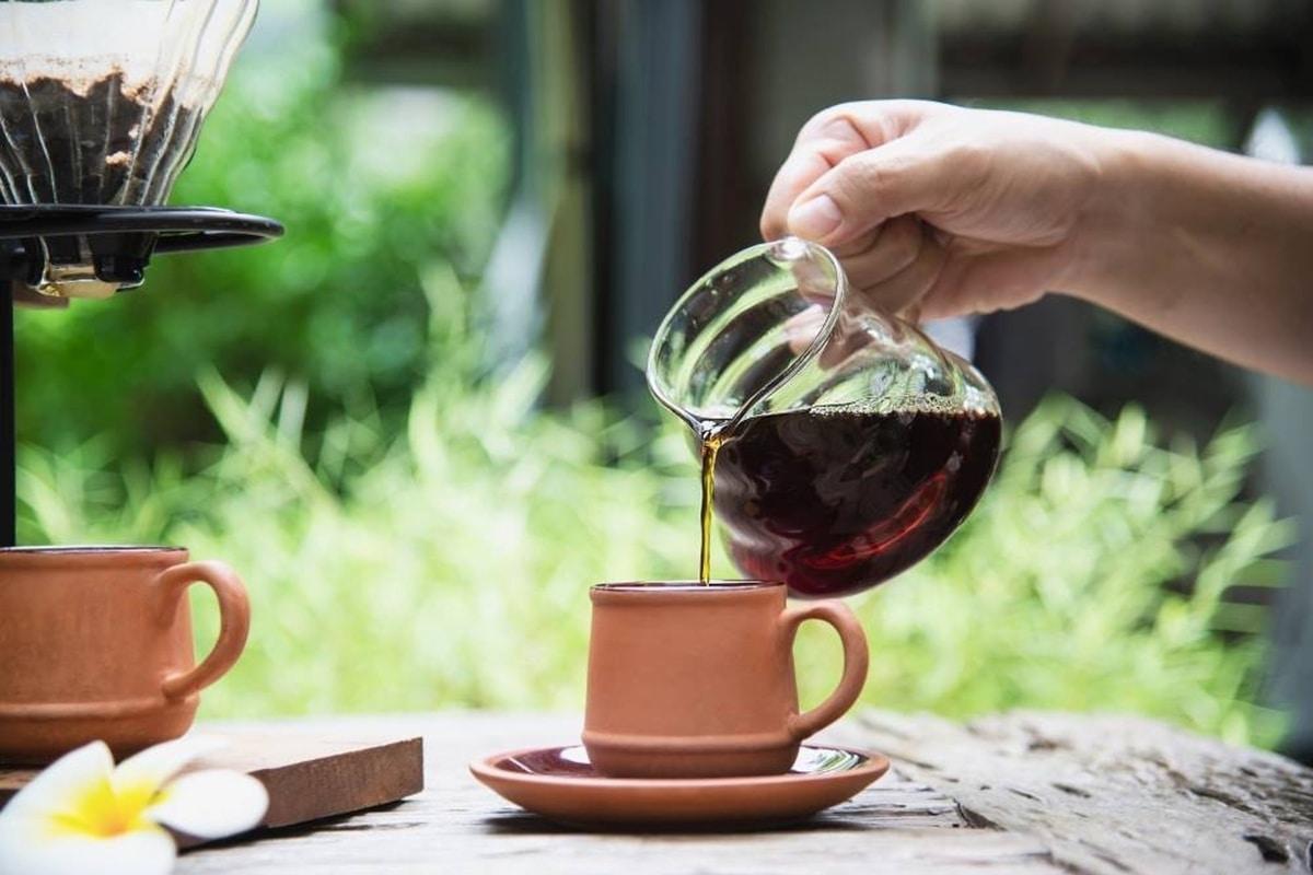 Hand pouring CBD coffee into a brown pottery mug